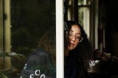 Arts Assistant Sara Galoua inspects a broken door; gloves on.