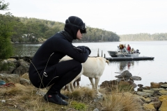 """'Callan' contemplating the temperature of Tassie water in late April, with one of """"Dorothy's"""" dogs, Maz."""