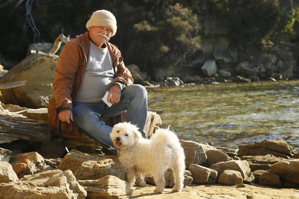 An image of Pete Hay (notepad in hand) and Ollie, on the seashore.